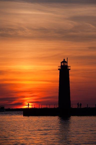 The Muskegon Lighthouse With a Lone Fisherman Silhouetted