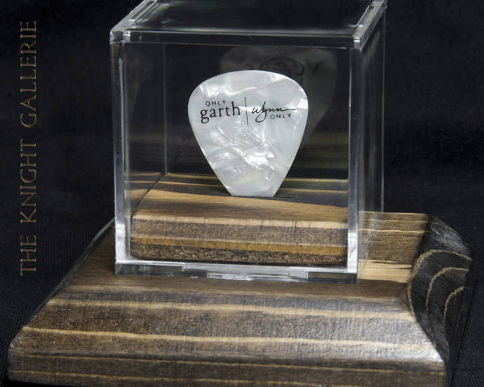 Stage-used Garth Brooks guitar pick with display case and matching pedestal