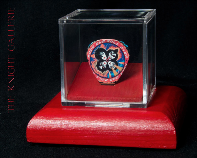 Commemorative guitar pick in a display case: KISS