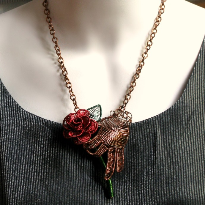 Unique wire woven pendant with hand holding red rose