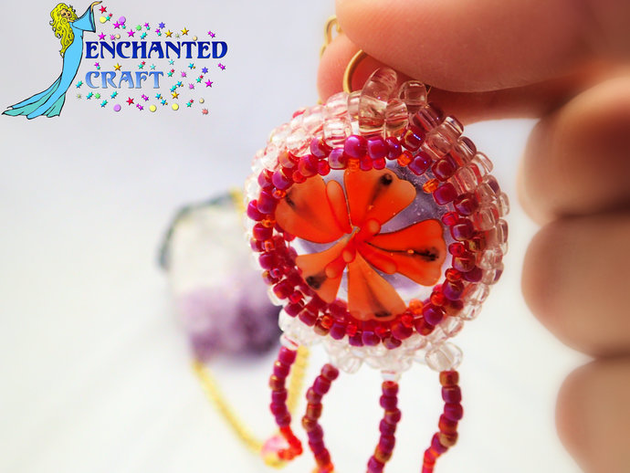 Bright orange red lampworked flower beaded pendant on a gold tone chain