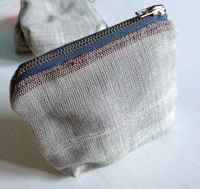 Small zipper purse for money, makeup, or other things that ends up in the bottom