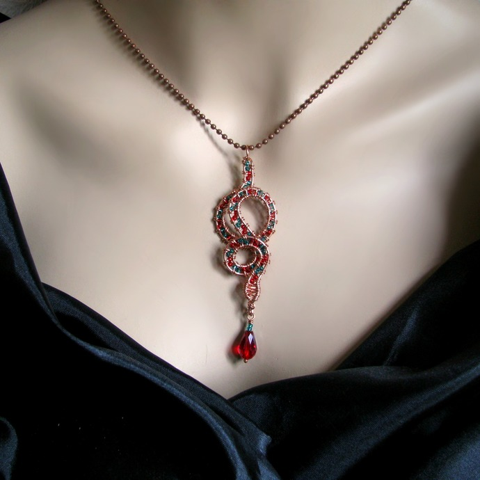 Wire wrapped snake pendant with red and green seed beads