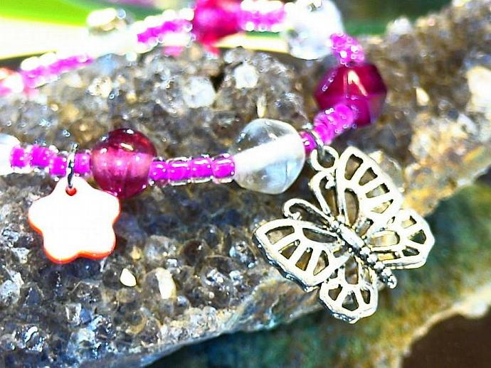 Pink beaded bracelet with butterfly and shell flower charms