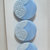Schwanda Card of Light Blue Glass Buttons with White Enamel Paint Lace Design