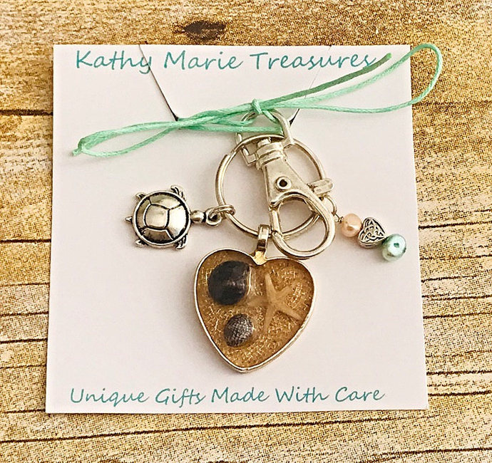 Hand poured resin key ring with beach sand and minature shells. Tiny sea star