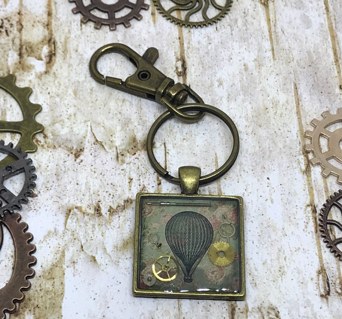 Steampunk air balloon image with gears and cogs set in resin bag charm, fantasy