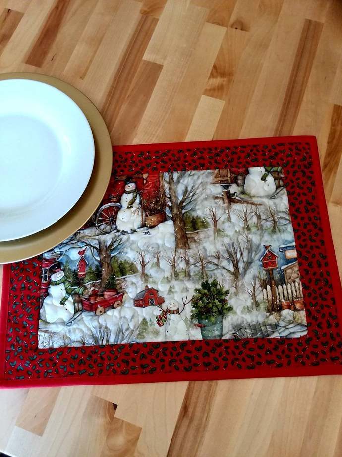 4 Piece set of snowmen with a snow scene place mats that measure 19 by 14 inches