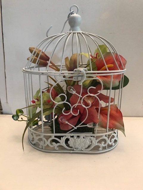 Tropical silk flowers in white bird cage