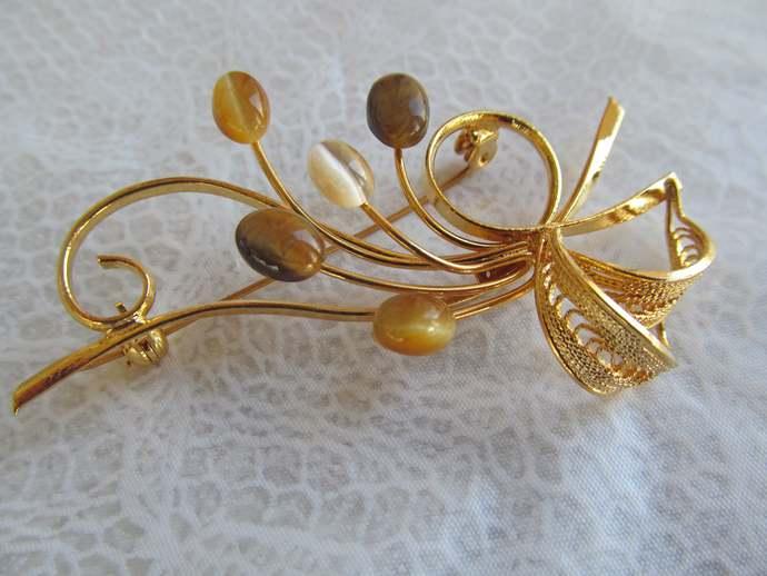 Signed Swoboda floral spray with genuine tiger eye gemstone w gold colored metal