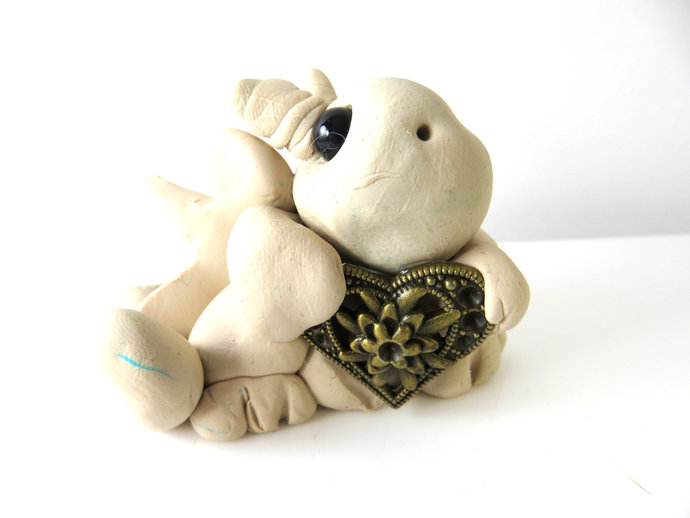 Clay baby dragon sculpture figurine with a gold heart