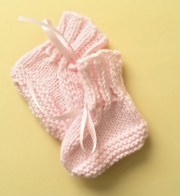 Pink hand knitted newborn to 3 months baby booties trimmed with matching ribbon.