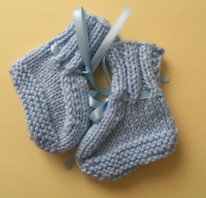 Blue hand knitted newborn to 3 months baby booties trimmed with matching ribbon.