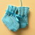 Teal hand knitted newborn to 3 months baby booties trimmed with matching ribbon.