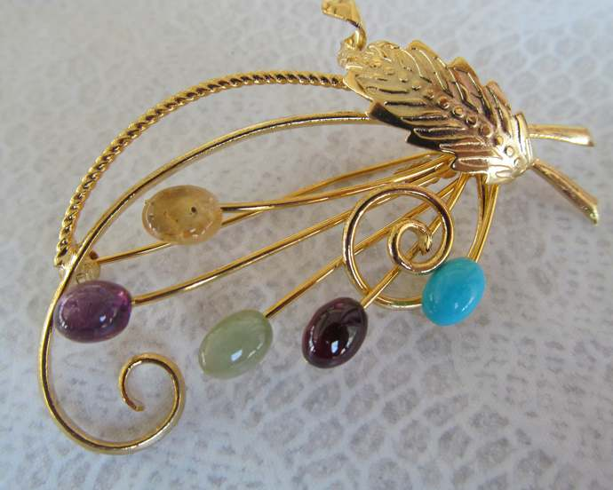Signed Swoboda floral spray with genuine multi gemstones w gold colored metal