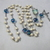 Catholic rosary with white wooden beads and turquoise lampwork Our Fathers with