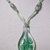 Green glass pendant with a semi-floral motif on green ribbon decorated with