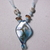 Turquoise and copper color glass pendant on turquoise ribbon decorated with