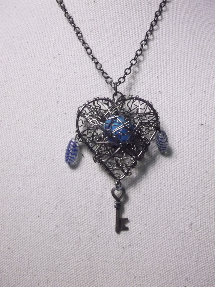 Wire wrapped heart with turquoise bead in center dangling key and dangling glass