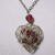 Gold color wire wrapped heart pendant with red glass beads in center and a red