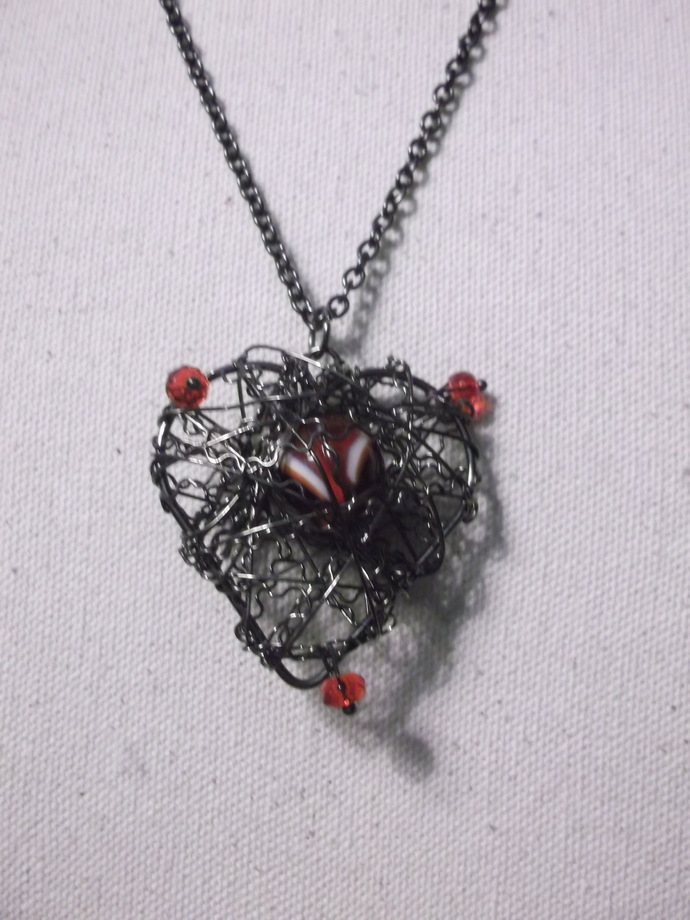Antiqued black wire wrapped heart pendant with red and white marble in center,