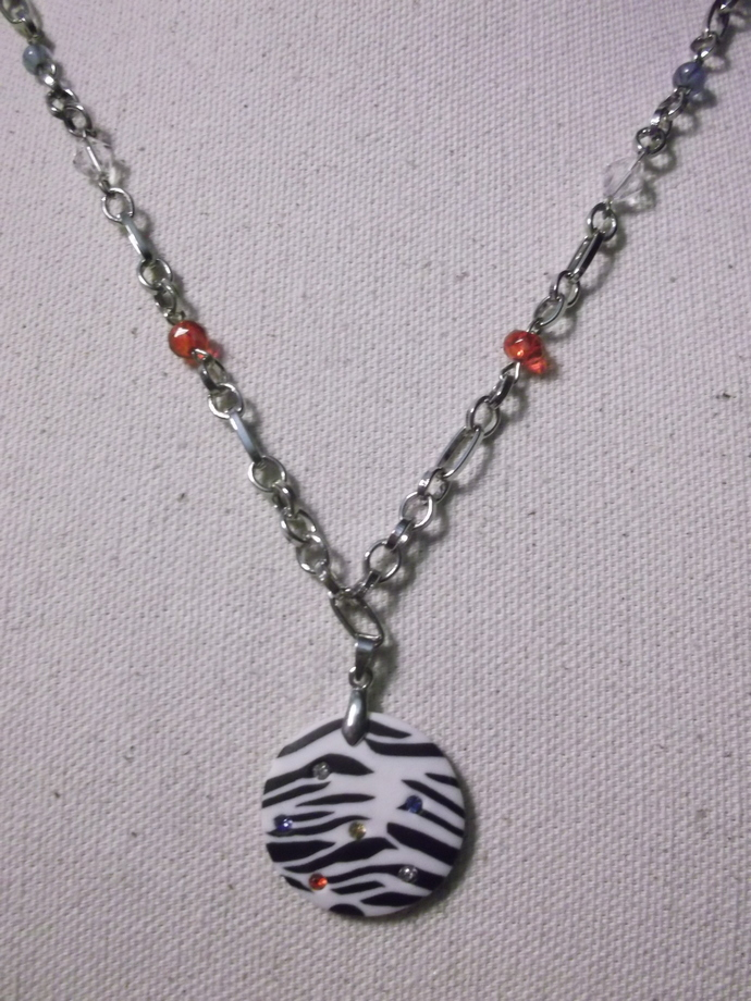 Zebra striped polymer clay pendant with tiny multi-color embedded rhinestones on