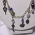 Gold color base metal chain necklace with gold color charms accented with blue,