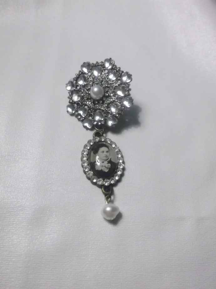 Rhinestone adorned pendant with a faux pearl with dangling portrait of an old