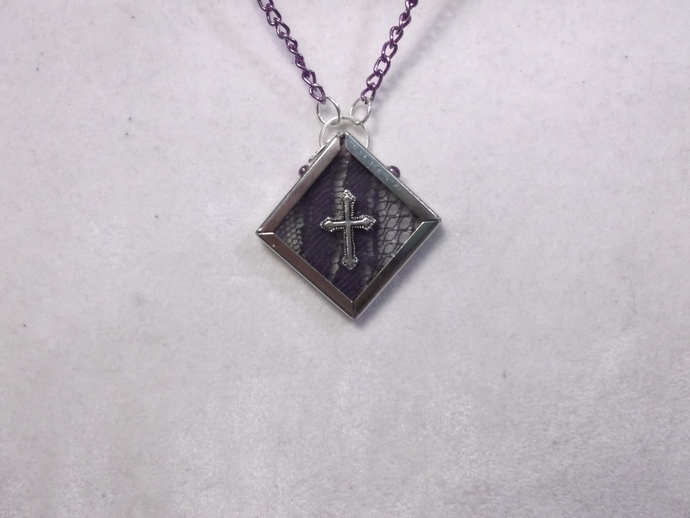 Silver color cross on glass encased purple lace pendant necklace hanging on