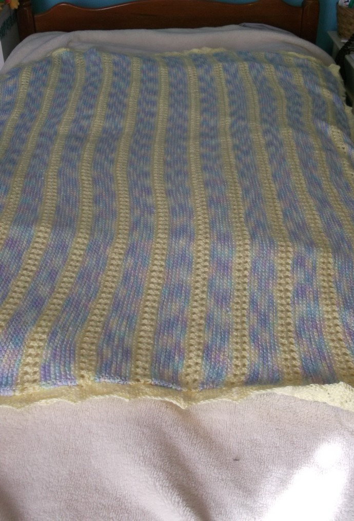 Knit baby blanket yellow and multi-color yarn in pastel yellow, blue, lavender