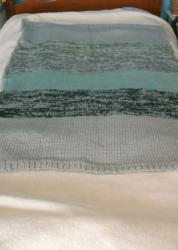 Knit baby blanket in green and gray in stockinette stitch with garter stitch