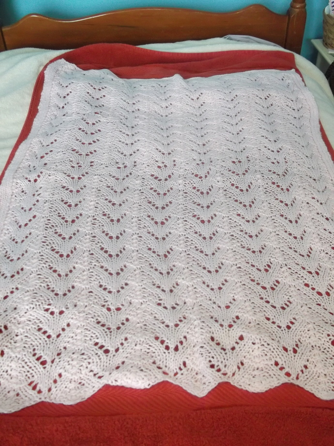 Knit baby blanket pink in a lace pattern
