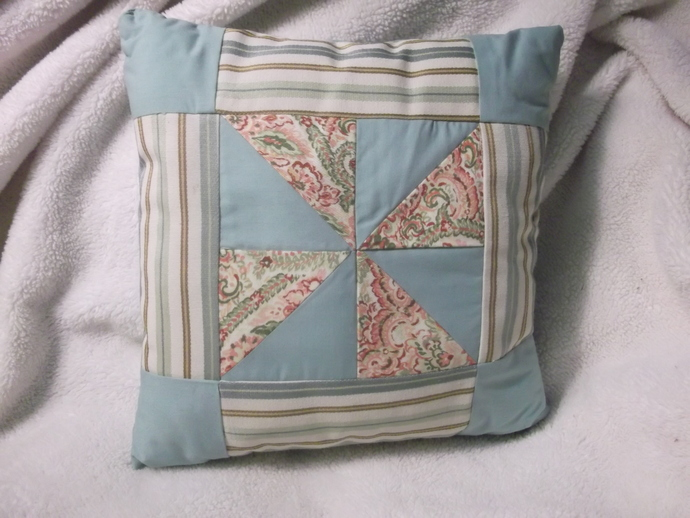 Paisley print, and green fabric windmill design quilt pillow with striped fabric
