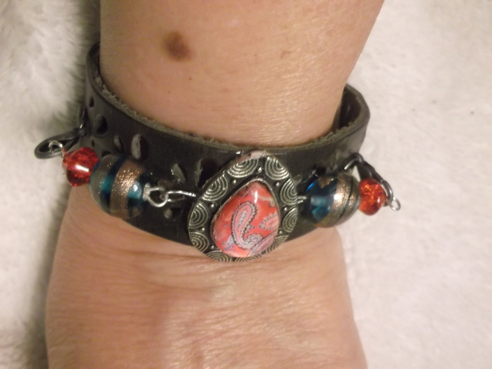 Leather band bracelet with flower design cut out, paisley design resin coated