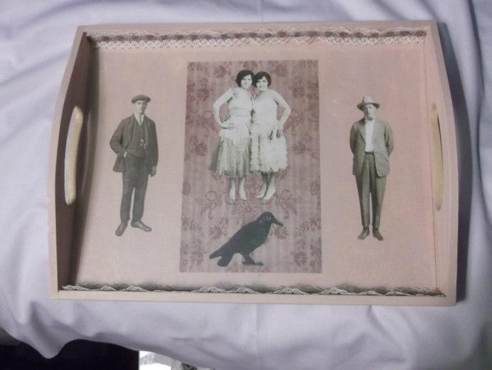 Beige colored tray with old fashioned people cut outs and a raven cut out