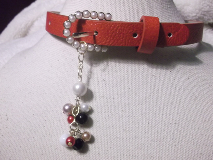 Red synthetic collar choker belt style with white, red, gold and black faux