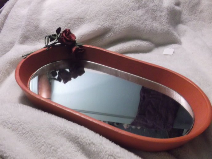 Rosy colored tray with glass bottom and faux roses in the corner comes with