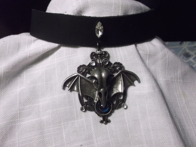 Skeletal bat head with wings and rhinestones on leather collar accented with
