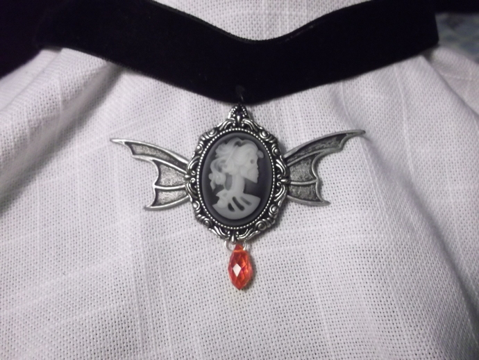 "Skeleton cameo with bat wings and red ""blood droplet"" bead on black velvet"