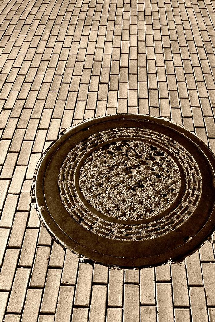 Manhole Covers and Converging Bricks Create A Strong Graphic