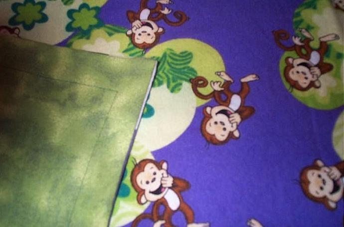 "100% cotton flannel blanket, approx. 34"" x 41"".  Purple background with monkeys"