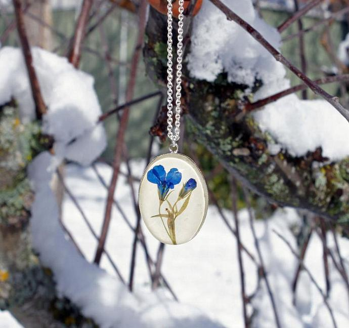 Blue necklace with real pressed blue Lobelia flowers and glass cabochon over