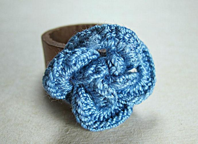 A leather ring decorated with four blue interlacing crochet rings which form a