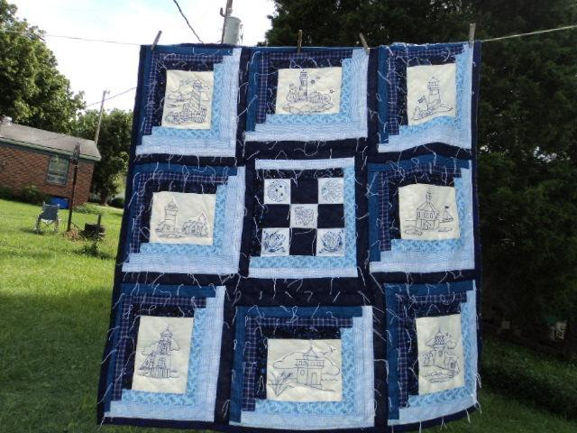 A  coverlet in blue lighthouses by the sea quilted and hand embroidered