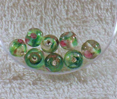 Pretty green and gold lampwork bead with roses on clear base 10mm S7