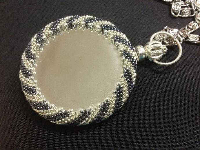 Magnifying mirror wrapped with handmade beadwork in silver and gunmetal,