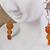 Orange glass dangle earrings. with Tibetan silver daisy spacers