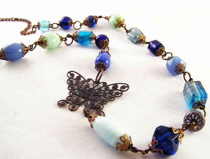 Blue glass necklace with copper butterfly filigree