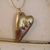 Steampunk broken heart pendant in copper and gold with copper stitches